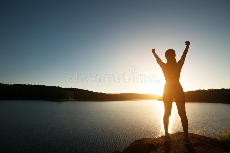 A silhueta da mulher consegue a caminhada no pico com por do sol da opinião do lago fotos de stock