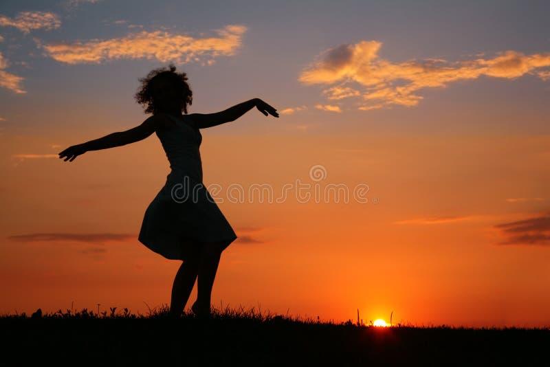 Silhueta da mulher da dança no por do sol foto de stock royalty free