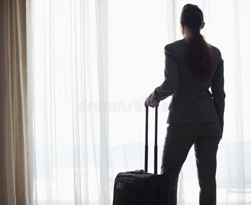 Silhueta da mulher de negócio com o saco que olha na janela imagens de stock