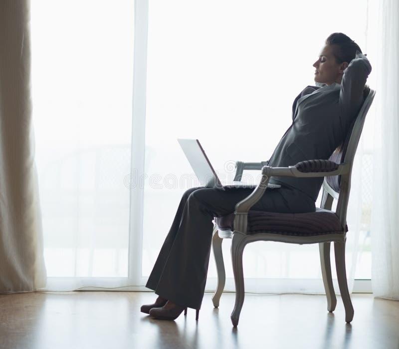 Silhueta da mulher de negócio que senta-se com portátil fotos de stock royalty free