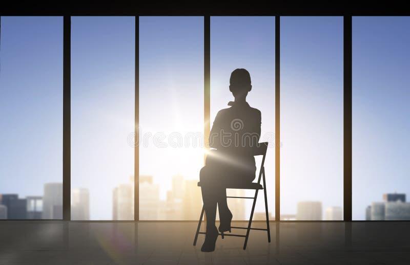 Silhueta da mulher de negócio que senta-se na cadeira ilustração do vetor