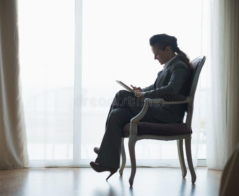 Silhueta da mulher de negócio que trabalha no PC da tabuleta fotos de stock royalty free