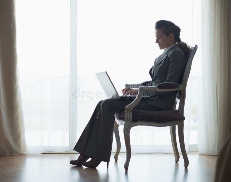 Silhueta da mulher de negócio que trabalha no portátil foto de stock