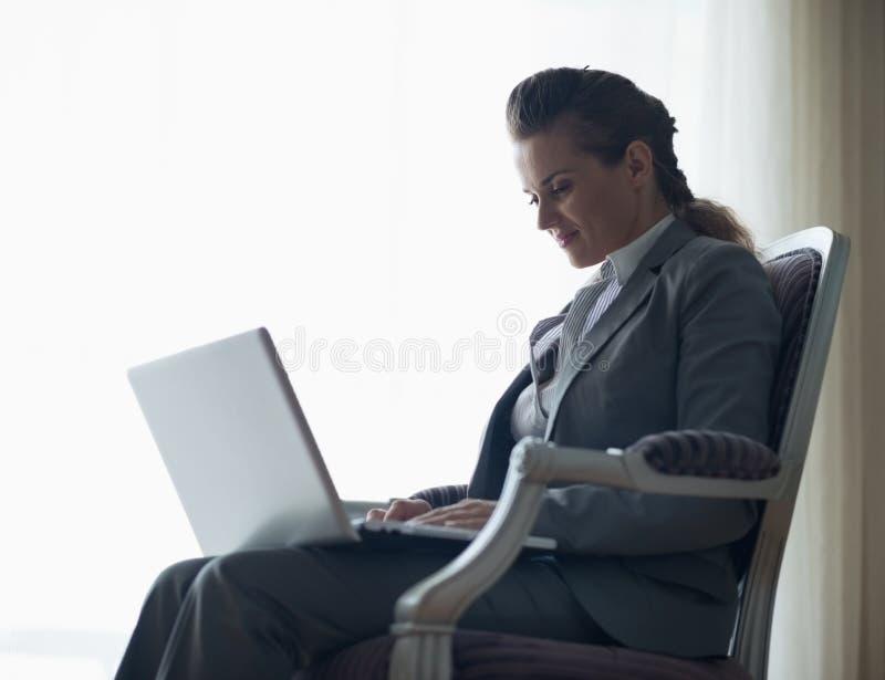 Silhueta da mulher de negócio que trabalha no portátil imagem de stock