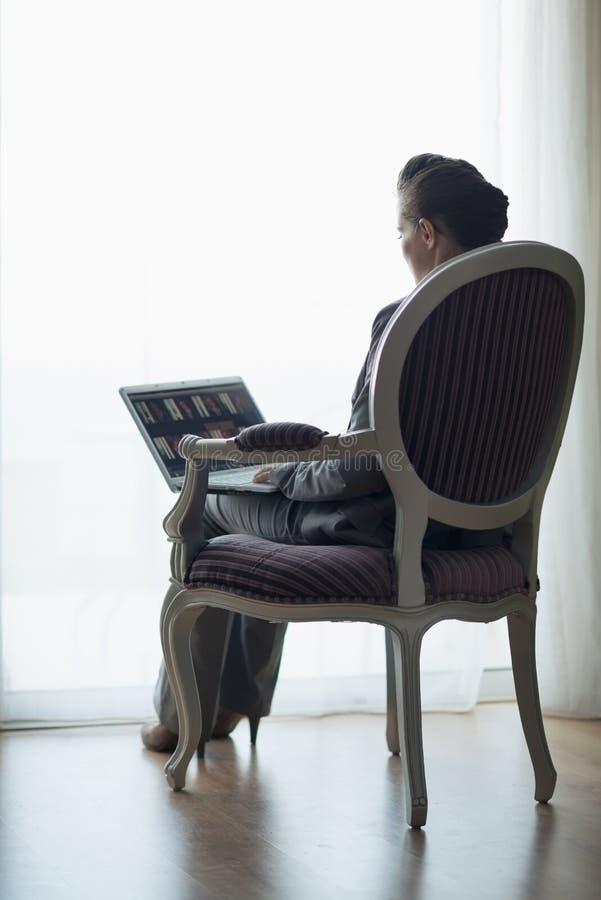 Silhueta da mulher de negócio que trabalha no portátil fotografia de stock