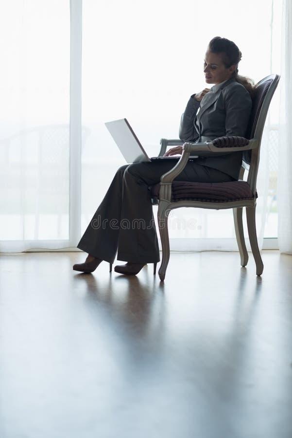 Silhueta da mulher de negócio que trabalha no portátil fotografia de stock royalty free