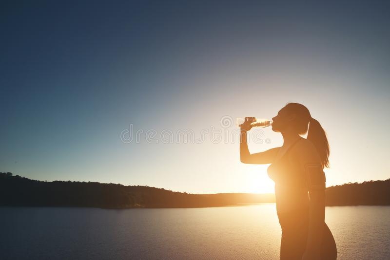 A silhueta da mulher do esporte caminha à parte superior da montanha e da bebida fotos de stock royalty free