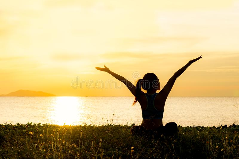 A silhueta da mulher do estilo de vida da ioga da meditação no por do sol do mar, relaxa vital fotografia de stock