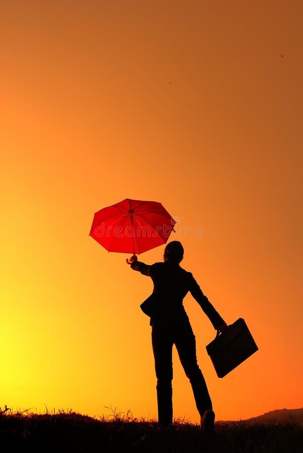 Silhueta da mulher e do por do sol de negócio do guarda-chuva imagem de stock royalty free