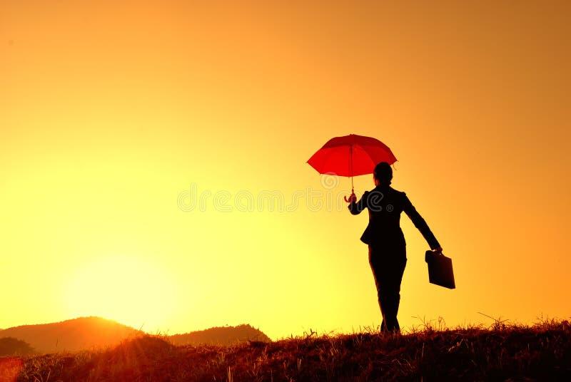 Silhueta da mulher e do por do sol de negócio do guarda-chuva fotos de stock