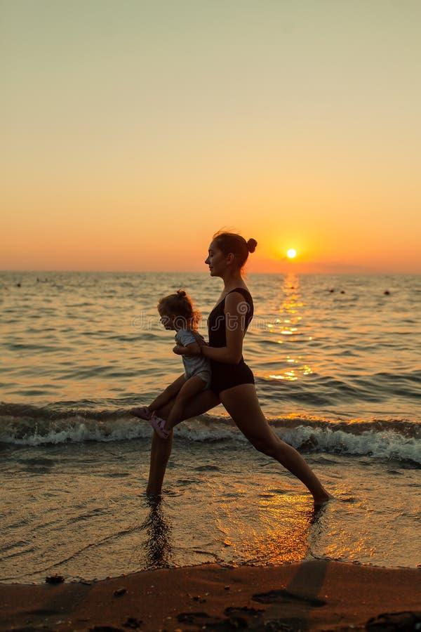 Silhueta da mulher e da menina que pratica equilibrando a pose do guerreiro da ioga junto durante o por do sol do oceano com o cé fotos de stock royalty free