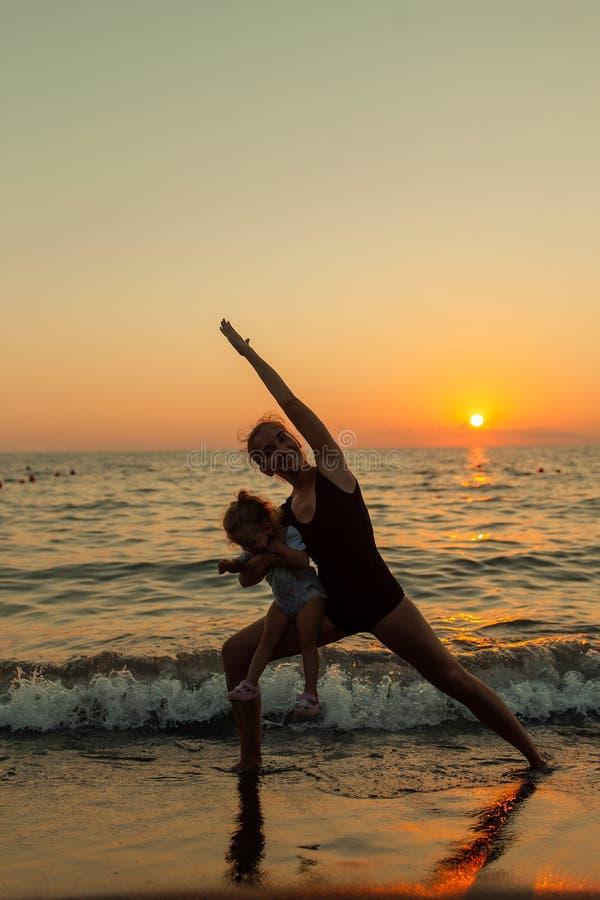 Silhueta da mulher e da menina que pratica equilibrando a pose do guerreiro da ioga junto durante o por do sol do oceano com o cé foto de stock