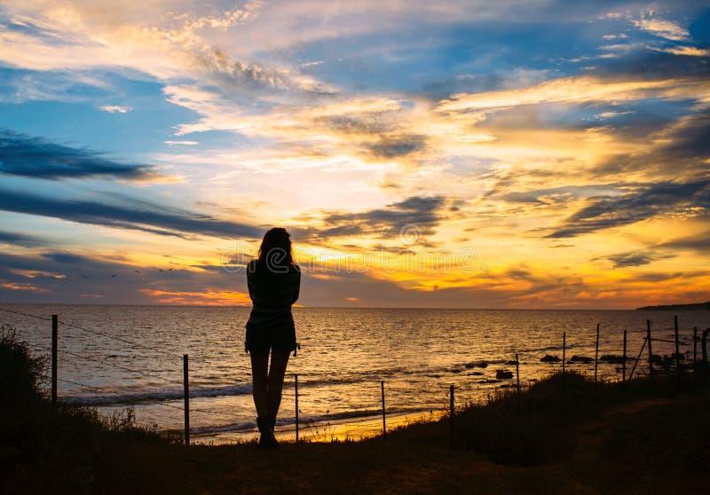 A silhueta da mulher está na praia no por do sol fotografia de stock royalty free