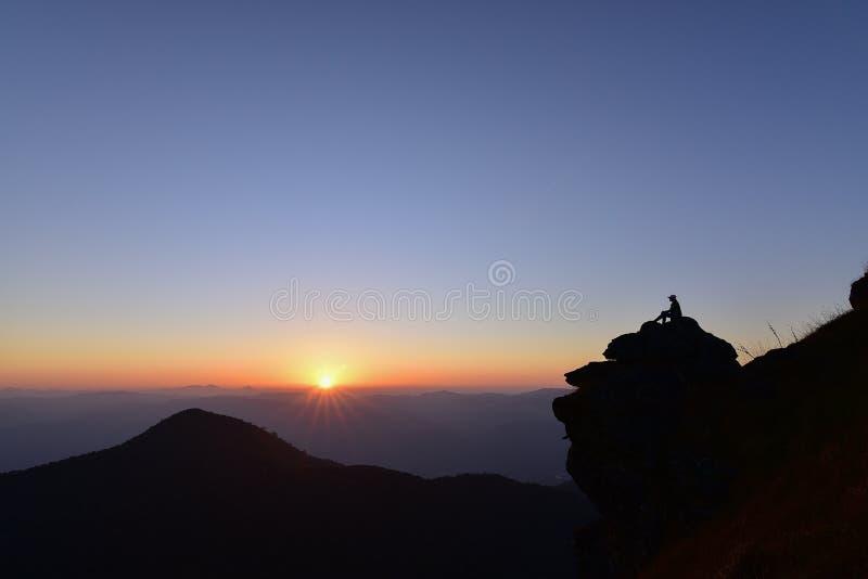 A silhueta da mulher estava sentando-se nas rochas na montanha foto de stock