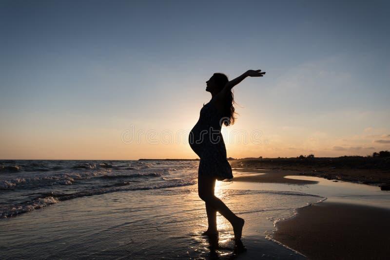Silhueta da mulher gravida que faz a ioga e o exercício na praia no por do sol do mar imagem de stock