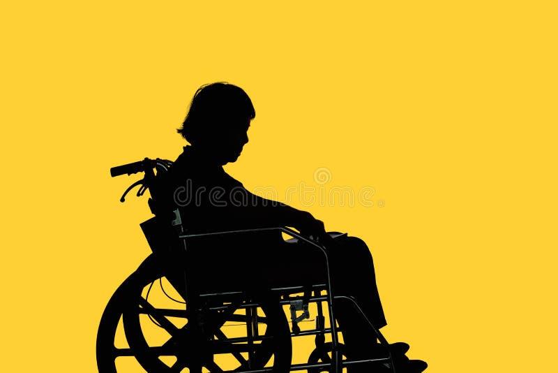 Silhueta da mulher idosa deficiente que senta-se em sua cadeira de rodas fotos de stock royalty free