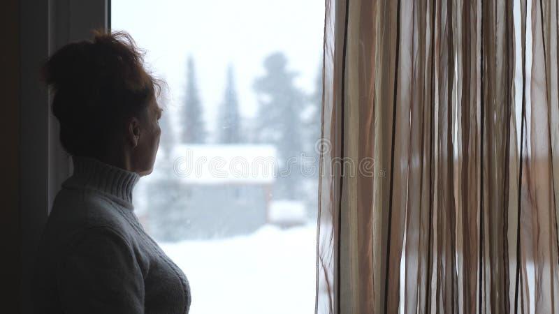 Silhueta da mulher madura na observação envelhecida na janela em montanhas nevado fotos de stock