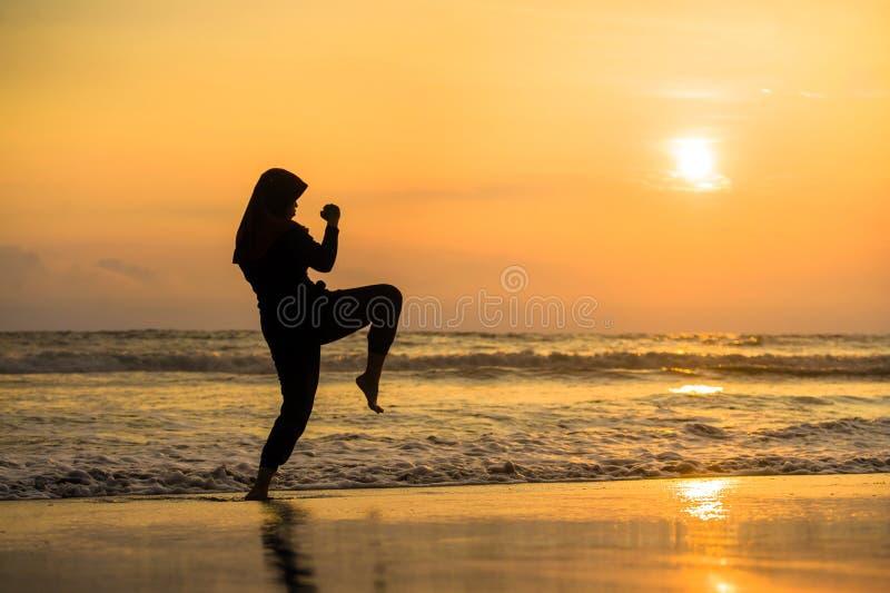 Silhueta da mulher muçulmana apta nova coberta no ataque e na aptidão de formação do pontapé do karaté das artes marciais do lenç imagens de stock royalty free