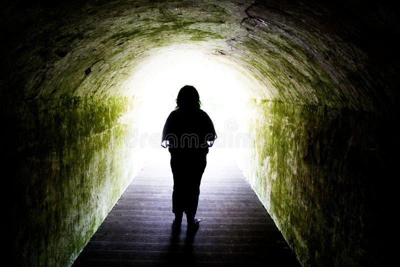 Silhueta da mulher na luz na extremidade do túnel fotos de stock royalty free