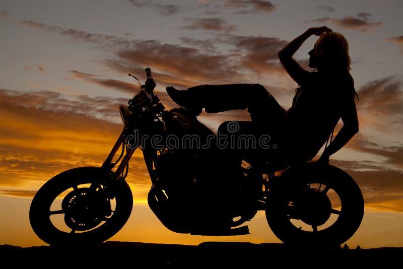 Silhueta da mulher no pé do cabelo da mão da motocicleta acima imagem de stock royalty free