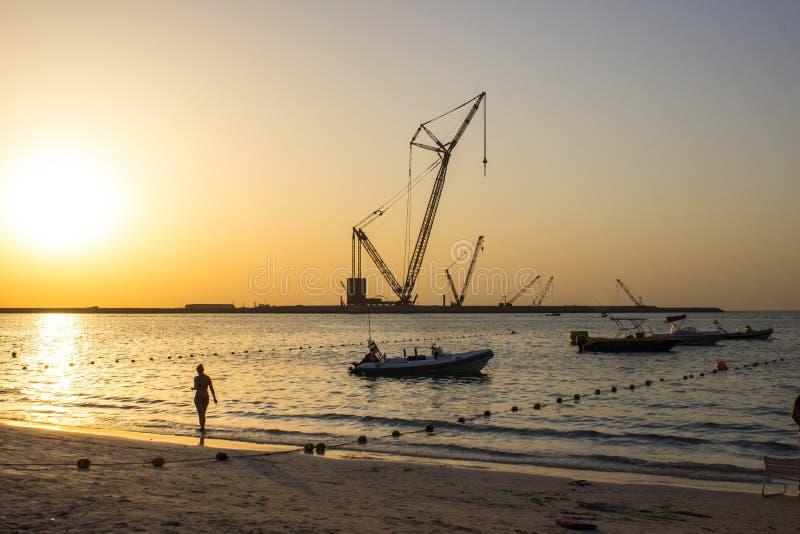 A silhueta da mulher no por do sol da praia imagem de stock
