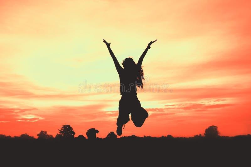 Silhueta da mulher no por do sol, salto da mulher, fotografia de stock