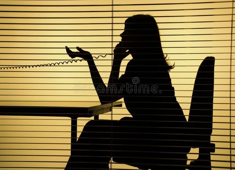Silhueta da mulher no telefone fotografia de stock