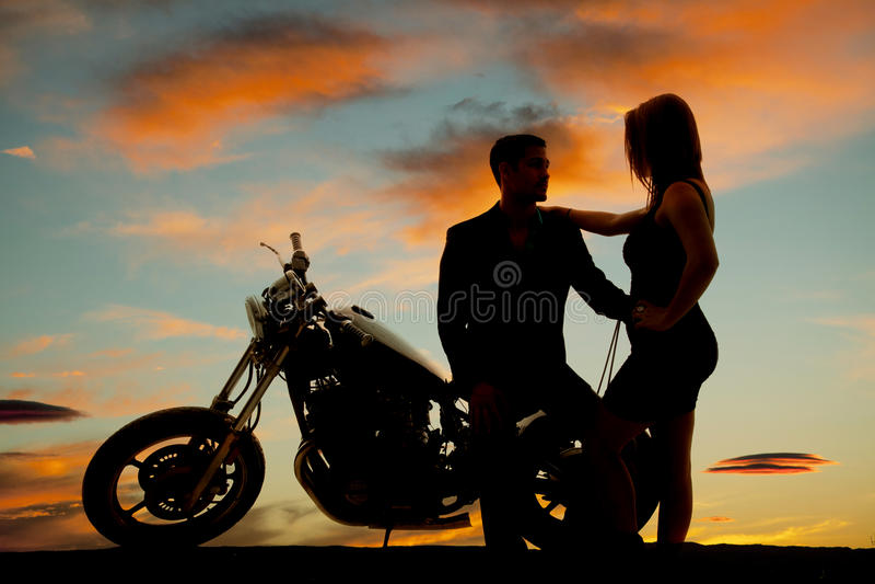 Silhueta da mulher pelo homem na motocicleta imagem de stock royalty free