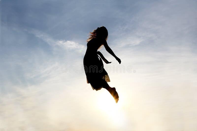 Silhueta da mulher que aumenta no céu imagem de stock