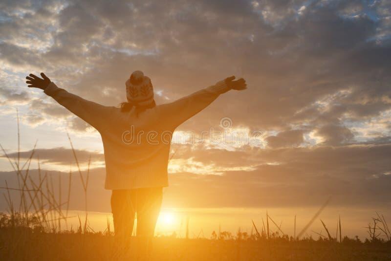 Silhueta da mulher que está no campo durante o por do sol imagens de stock royalty free