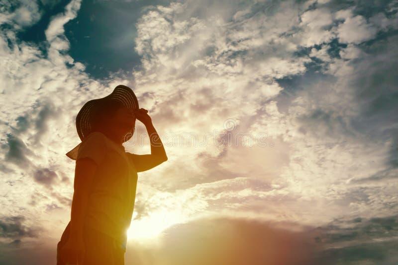 Silhueta da mulher que olha ao céu no tempo do por do sol imagem de stock