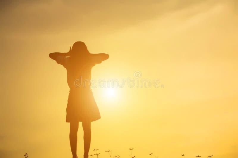 Silhueta da mulher que reza sobre o fundo bonito do c?u foto de stock royalty free