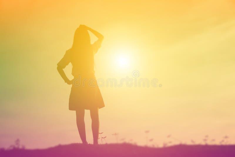 Silhueta da mulher que reza sobre o fundo bonito do c?u imagens de stock royalty free