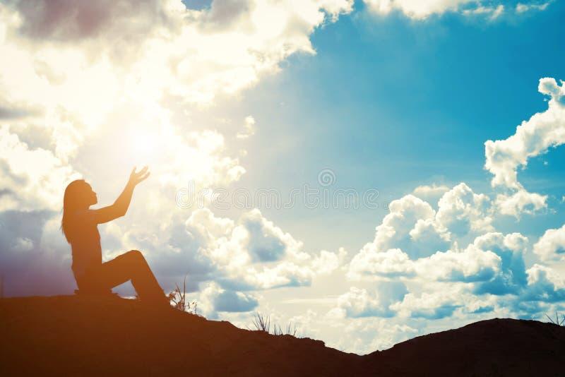 Silhueta da mulher que reza sobre o nascer do sol bonito imagem de stock