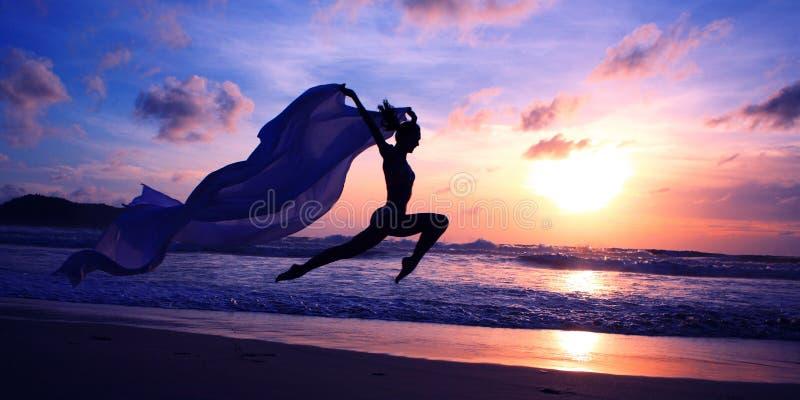Silhueta da mulher que salta na praia fotos de stock