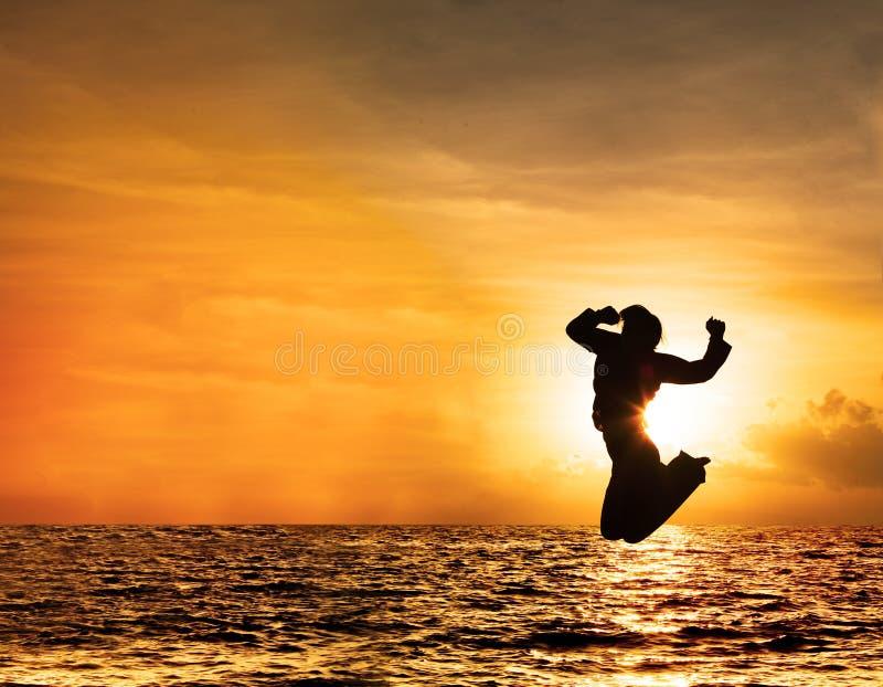 Silhueta da mulher que salta no por do sol fotos de stock royalty free