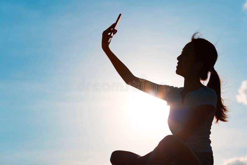 Silhueta da mulher que toma o selfie com o telefone celular com o backgr fotografia de stock