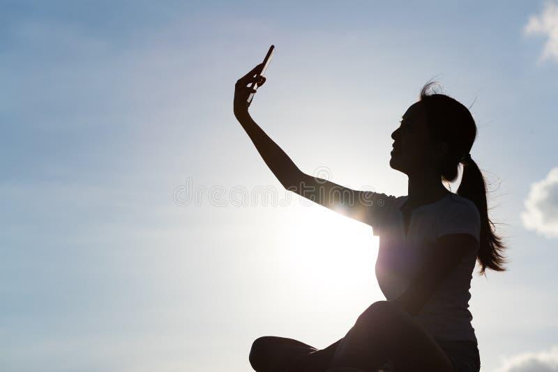 Silhueta da mulher que toma a selfie com o telefone celular sob a skyline me imagens de stock royalty free
