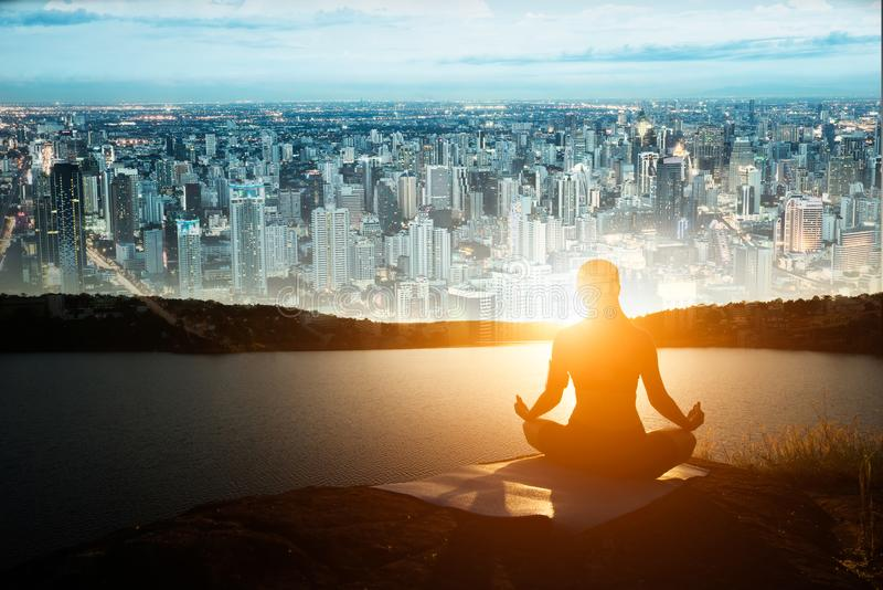 A silhueta da mulher saudável está praticando a ioga no lago da montanha fotografia de stock