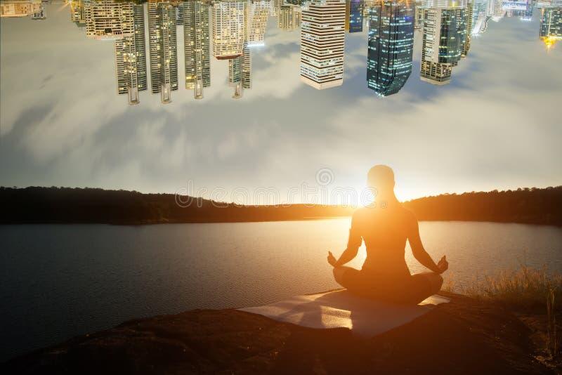 A silhueta da mulher saudável está praticando a ioga no lago da montanha imagem de stock