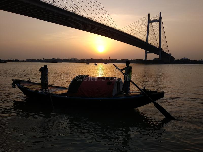 Silhueta da navigação do barco sobre o ganga do rio no crepúsculo com a ponte vidyasagar no fundo durante o por do sol imagens de stock