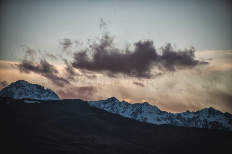 Silhueta da nuvem do por do sol da montanha da neve imagem de stock