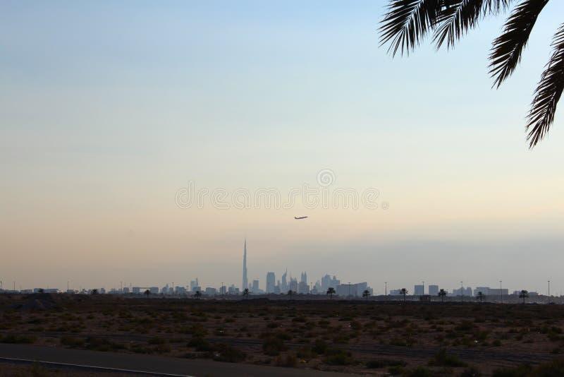 Silhueta da palmeira da data do céu do skylne do avião do khalifa do burj da skyline de Dubai do feriado do curso fotografia de stock