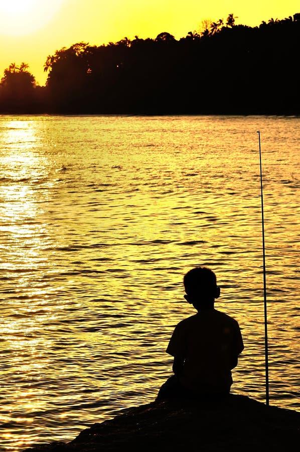 Silhueta da pesca da criança perto da praia fotos de stock