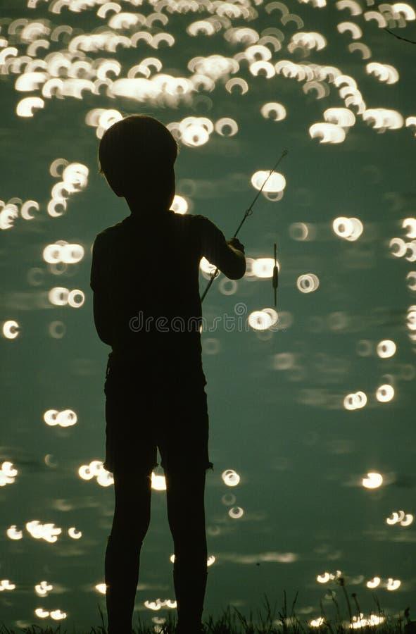 Silhueta da pesca do menino imagens de stock