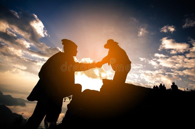 Silhueta da pessoa de ajuda dos povos na montanha na manhã fotografia de stock royalty free
