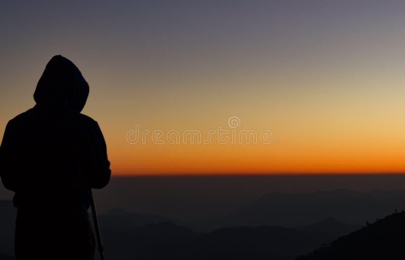 Silhueta da posição do fotógrafo do curso com uma câmera montada em um tripé e em disparar um lapso de tempo do nascer do sol/por fotografia de stock royalty free