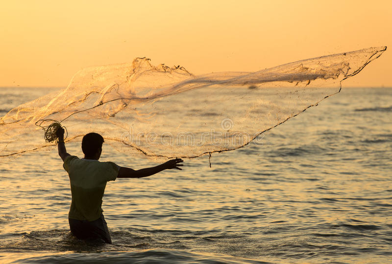 Silhueta da rede de jogo do pescador indiano não identificado no mar imagem de stock royalty free