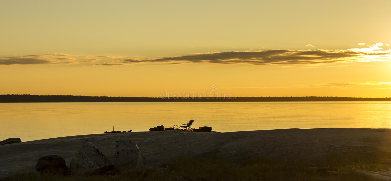 Silhueta da sala de estar do chaise na praia Mar calmo silencioso no por do sol Carélia, Rússia Fundo natural alaranjado fotos de stock royalty free
