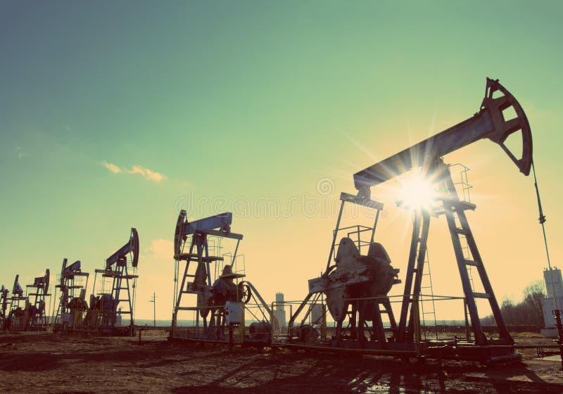 Silhueta das bombas de óleo contra o sol - estilo retro do vintage fotografia de stock royalty free